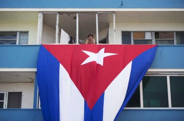 Un cubano, en la terraza de su vivienda donde cuelga la bandera cubana, cerca de la embajada de EEUU. Reuters