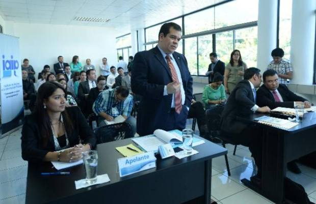 Xenia Hernández y Roberto Burgos, de Funde-Alac, exponen ante el IAIP que datos sobre viajes y publicidad son públicos y no pueden restringirse. A la derecha, los representantes del gobierno.