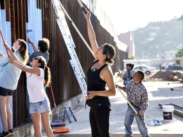 Los vecinos de Nogales ayudan a la artista a pintar la frontera. / Nick Oza (The Republic)