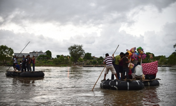 Migrants use a makeshift raft to cross the Suchiate river, natural border between Mexico and Guatemala, in Ciudad Hidalgo, Chiapas state, Mexico. Photograph: Yuri Cortez/AFP/Getty Images