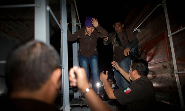 Immigration officials remove Central American migrants from a northbound freight train during an after-midnight raid by federal police in San Ramon, Mexico, last year. Photograph: Rebecca Blackwell/AP