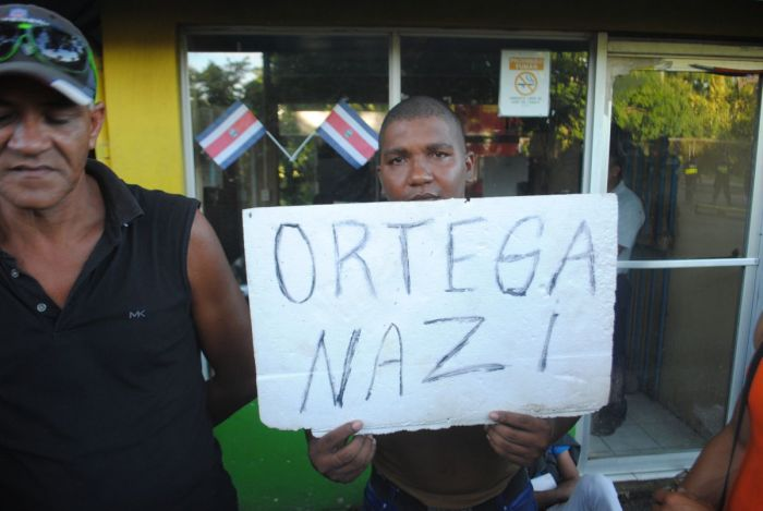 Cuban Ricardo Perez, 30, holds up an unflattering sign that compares Nicaragua's president to Der Führer