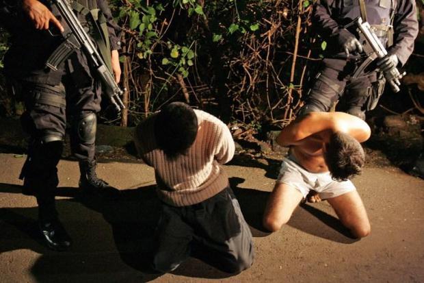 Imagen de archivo que muestra a dos agentes del Grupo de Reacción Policial (GRP), la unidad élite de la Policía Nacional Civil (PNC), que custodian a dos pandilleros de la Mara Salvatrucha, tras un operativo nocturno en el municipio de La Libertad. Foto Yuri Cortez (AFP).