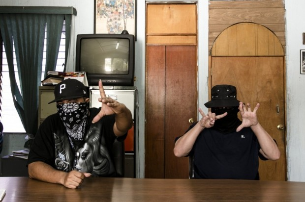 The spokesmen for the 18th Street gang Revolucionarios and MS-13 sit side by side making gang signs but discussing their truce. (Fred Ramos for The Washington Post)