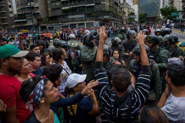 Un grupo de personas manifiestan contra miembros de la Guardia Nacional Bolivariana en Caracas en protesta por la carestía. MIGUEL GUTIERREZ EFE