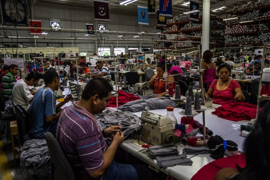 Workers filling T-shirt orders for American universities at a factory in Ciudad Arce, El Salvador, that makes an effort to hire former criminals. Credit Meridith Kohut for The New York Times