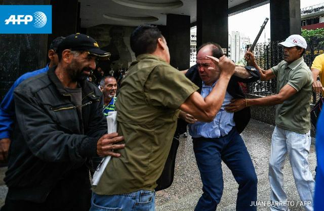El diputado Julio Borges es agredido frente a la sede del Consejo Nacional Electoral en Caracas. Fotografía de Juan Barreto. AFP