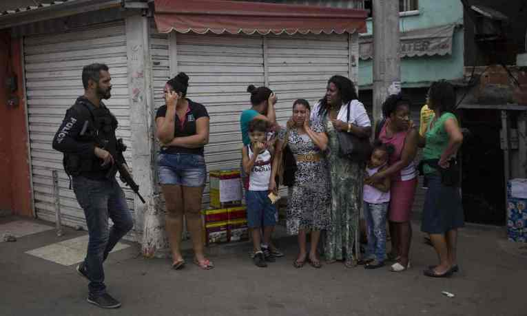 A police officer walks past distressed residents in the Alemão favela. Photograph: Felipe Dana/AP