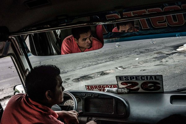 A bus driver in San Salvador in June. Fred Ramos / El Faro for The New York Times