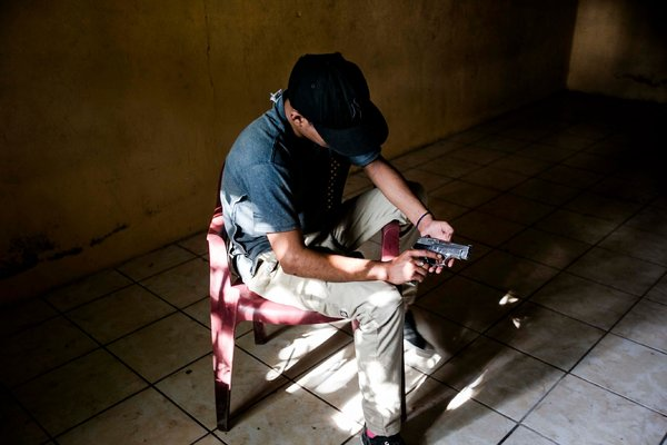 A 15-year-old gang member with a gun in a house in La Paz in July. Fred Ramos / El Faro for The New York Times