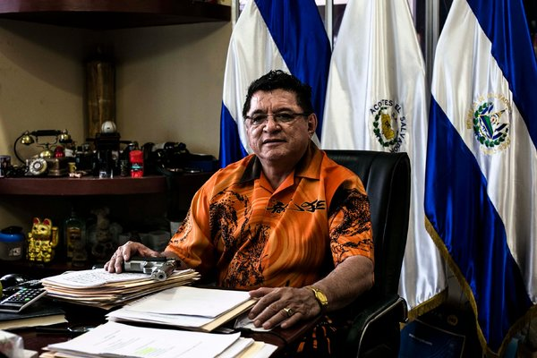 Catalino Miranda, with a gun on his desk in San Salvador, owns a fleet of buses and refuses to yield to extortion demands. Fred Ramos / El Faro for The New York Times