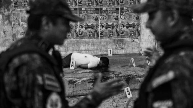 Policías mexicanos junto a un cadáver en Acapulco, la ciudad con una de las tasas más altas de homicidios. PEDRO PARDO (AFP)