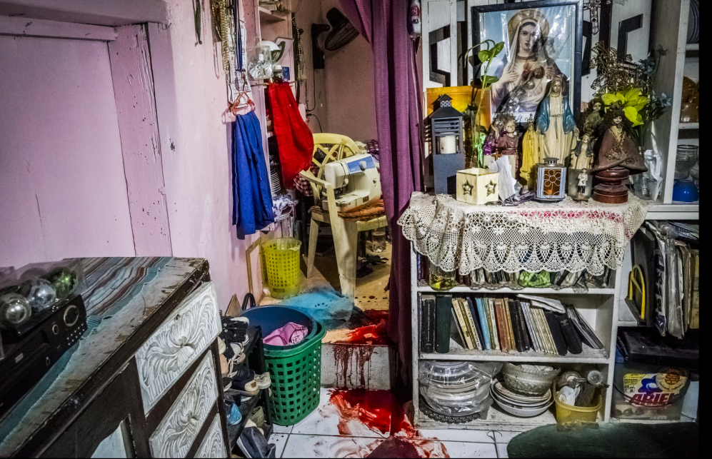 'Killed at home'. The blood of Florjohn Cruz, 34, stained the floor in his family's living room, next to an altar displaying images and statues of the Virgin Mary, among other items.